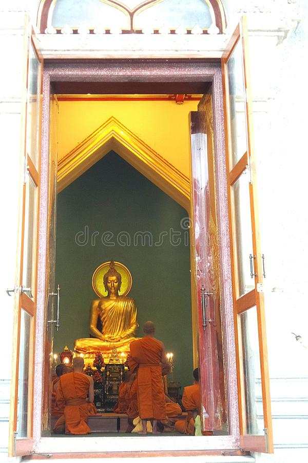 Mnicha buddyjskiego spełniania obrząd religijna przed główną świętą Złotą Buddha statuą w świątynnym pawilonie zdjęcia stock