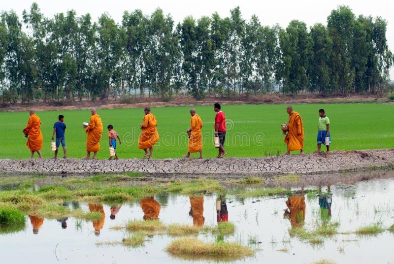 Mnichom buddyjskim dają karmowej ofiarze od ludzi spacerem obraz stock
