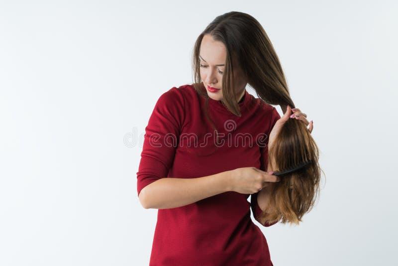 A moça à moda bonita penteia seu cabelo com um pente imagens de stock