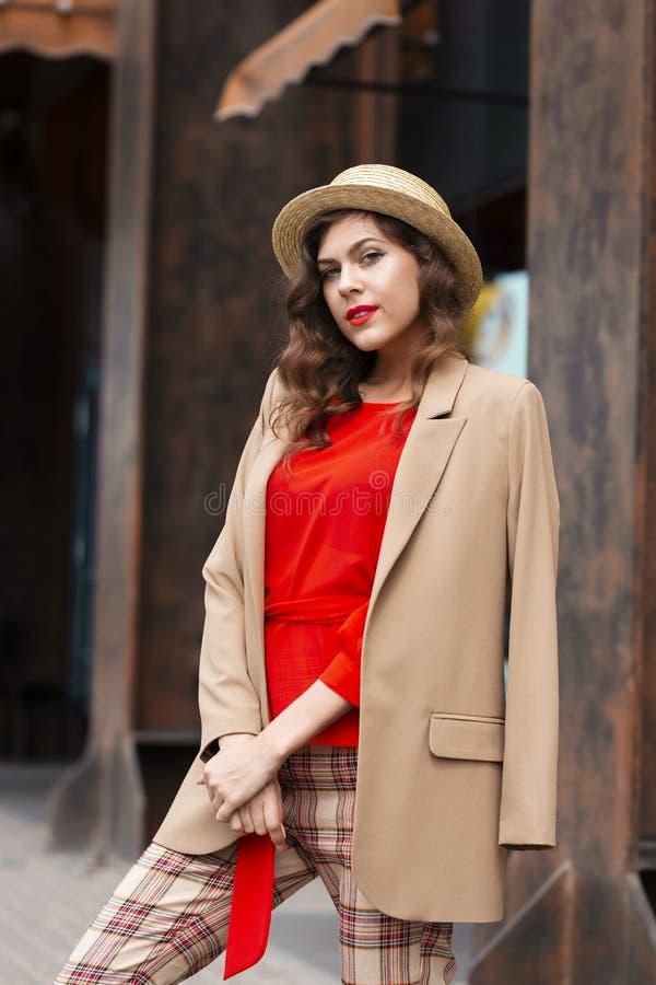 Moça à moda na roupa ocasional na moda vestida em poses de um revestimento e do chapéu na rua em um dia de verão foto de stock royalty free