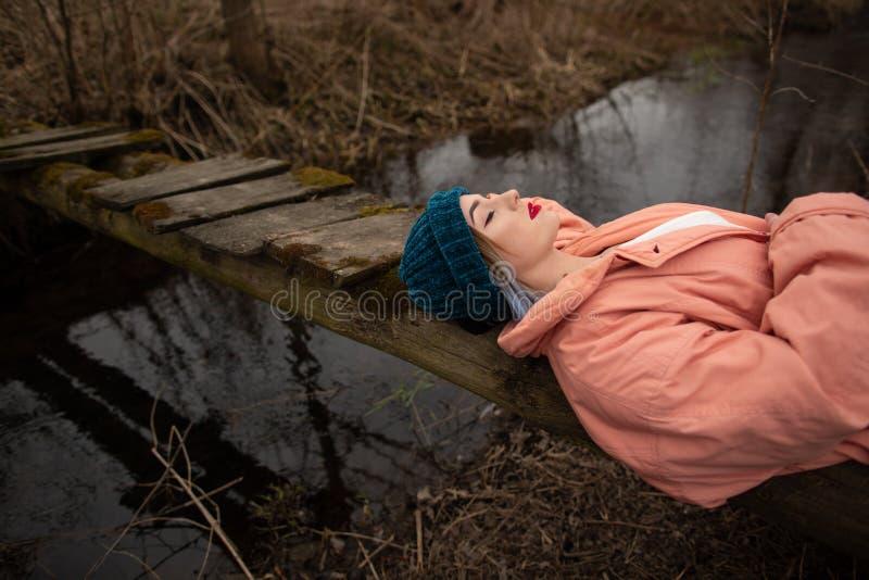 Moça à moda que descansa na costa do rio, encontrando-se em uma ponte de madeira pequena imagem de stock royalty free