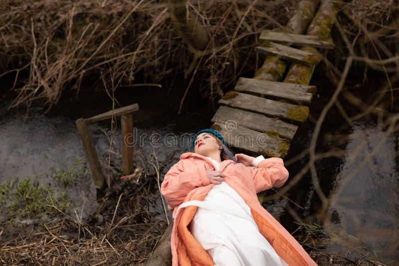 Moça à moda que descansa na costa do rio, encontrando-se em uma ponte de madeira pequena fotografia de stock