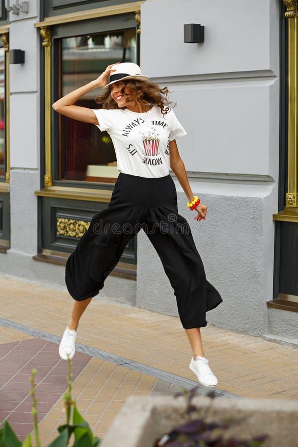 A moça à moda vestida em um t-shirt branco, em uma calças larga preta e em umas sapatilhas brancas está saltando na rua na fotografia de stock