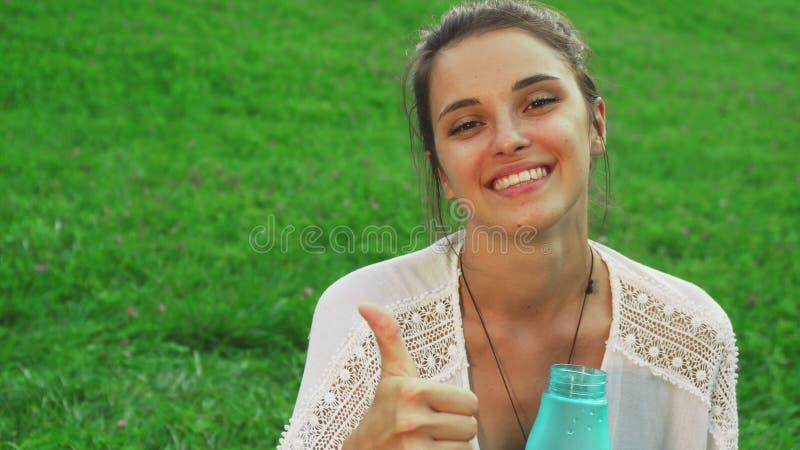 A moça é água potável ao fazer a ioga foto de stock royalty free