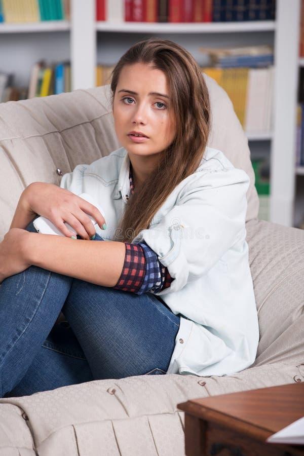 A moça é assento de grito no sofá foto de stock
