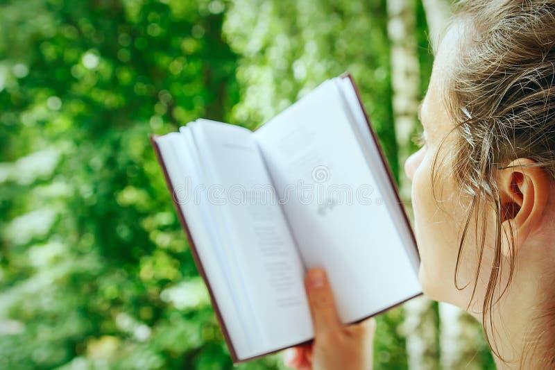 A moça é close-up do livro de leitura imagem de stock royalty free