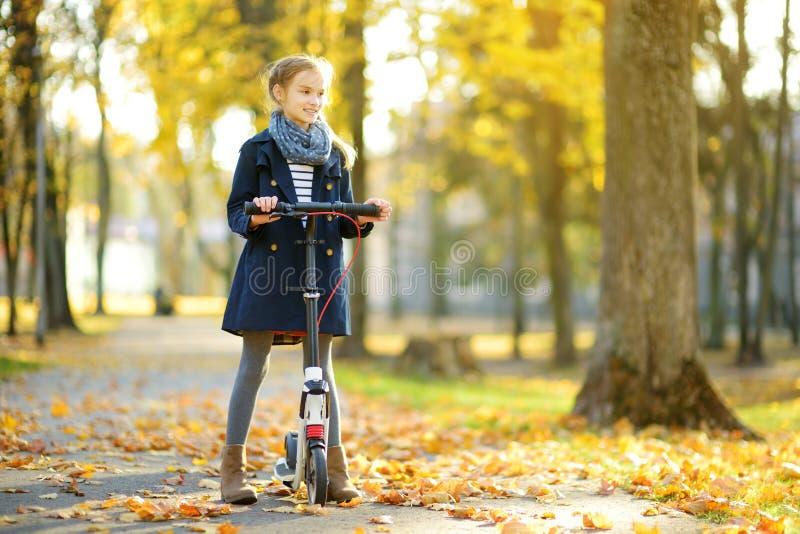 Moça adorável que monta seu 'trotinette' em um parque da cidade na noite ensolarada do outono Criança preteen bonita que monta um fotografia de stock