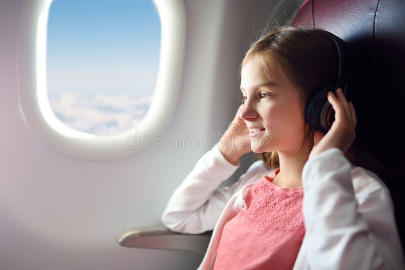 Moça adorável que viaja por um avião Criança que senta-se pela janela dos aviões e que olha fora ao escutar a música foto de stock