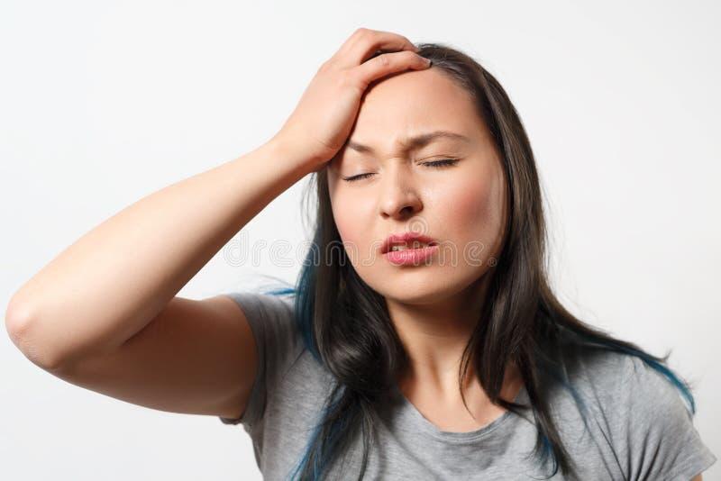 A moça agarra sua cabeça com sua mão e descreve uma dor de cabeça severa No fundo branco fotos de stock royalty free
