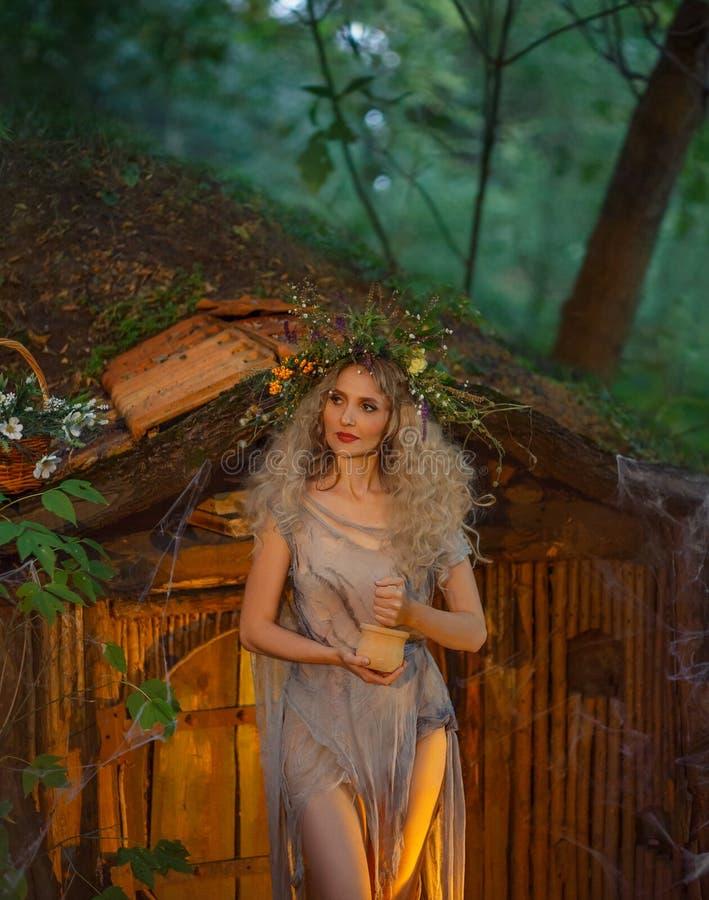 A moça agradável com cabelo louro com uma grinalda luxúria surpreendente em sua cabeça na floresta está agitando ervas atmosféric foto de stock royalty free
