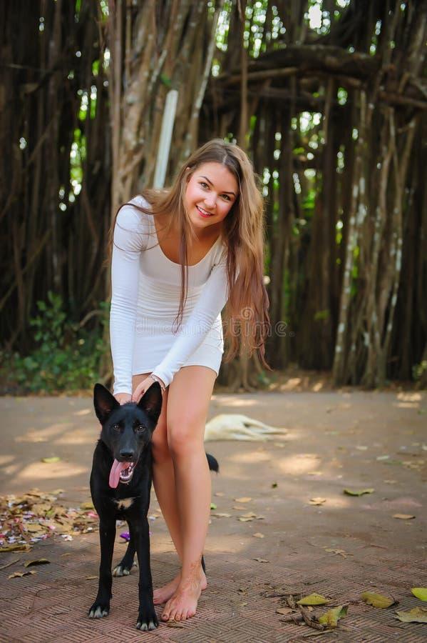 Moça alegre na caminhada no parque com seu amigo quadrúpede Mulher bonita no vestido curto e no cão preto que jogam fora imagem de stock