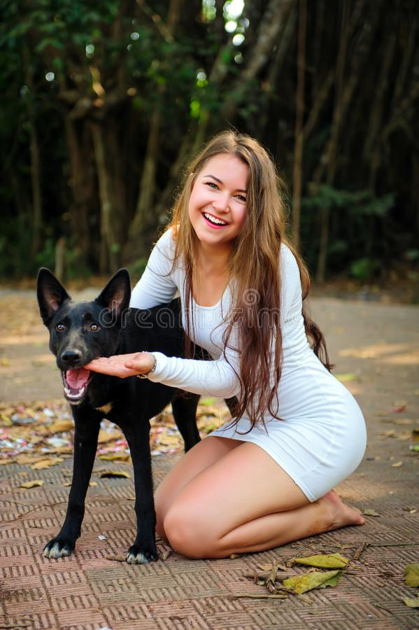 Moça alegre na caminhada no parque com seu amigo quadrúpede Mulher bonita no vestido curto e no cão preto que jogam fora fotos de stock