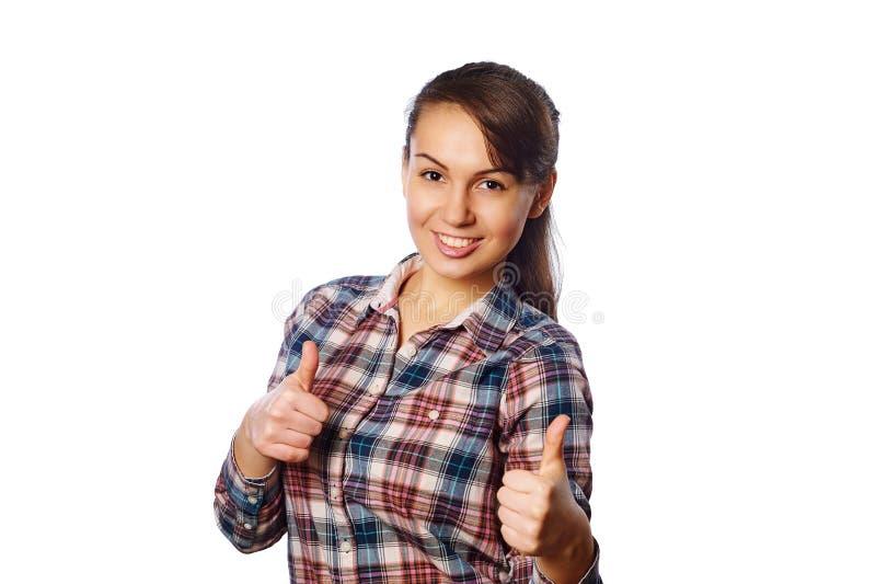 A moça alegre na camisa quadriculado que mostra os polegares acima com ambos cede o fundo branco fotos de stock royalty free