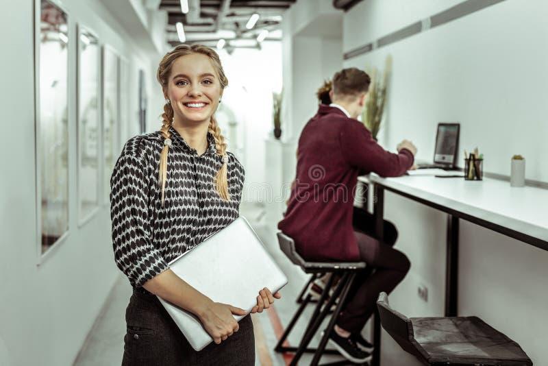 Moça alegre que é interno no escritório moderno foto de stock