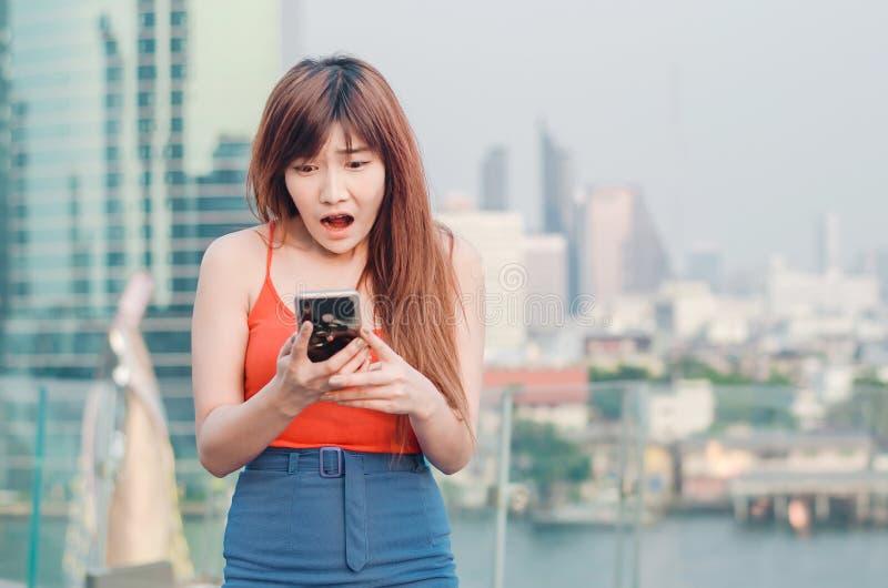 Moça ansiosa do retrato ascendente próximo que olha o telefone que vê más notícias ou fotos com emoção de desgosto em sua cara so imagem de stock royalty free