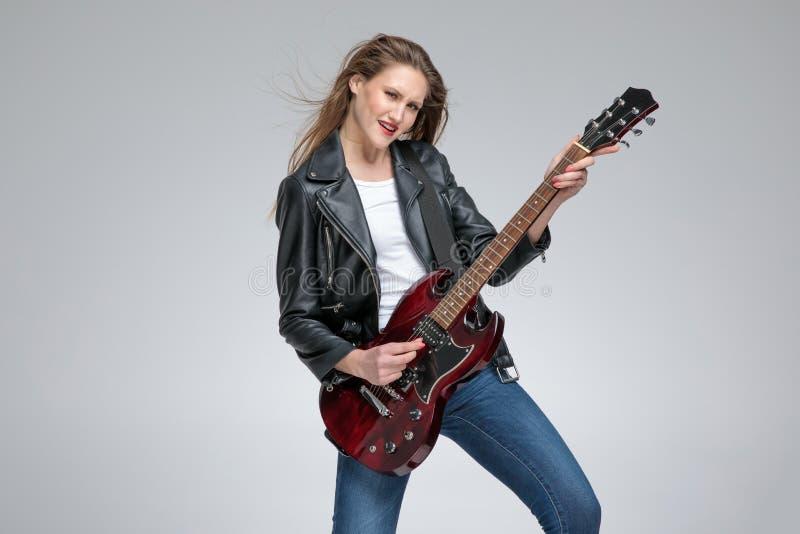 Moça apaixonado que joga a guitarra e que veste um casaco de cabedal fotos de stock
