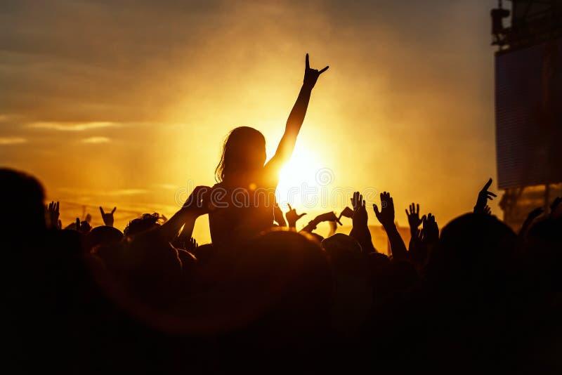 A moça aprecia um concerto de rocha, silhueta no por do sol foto de stock royalty free