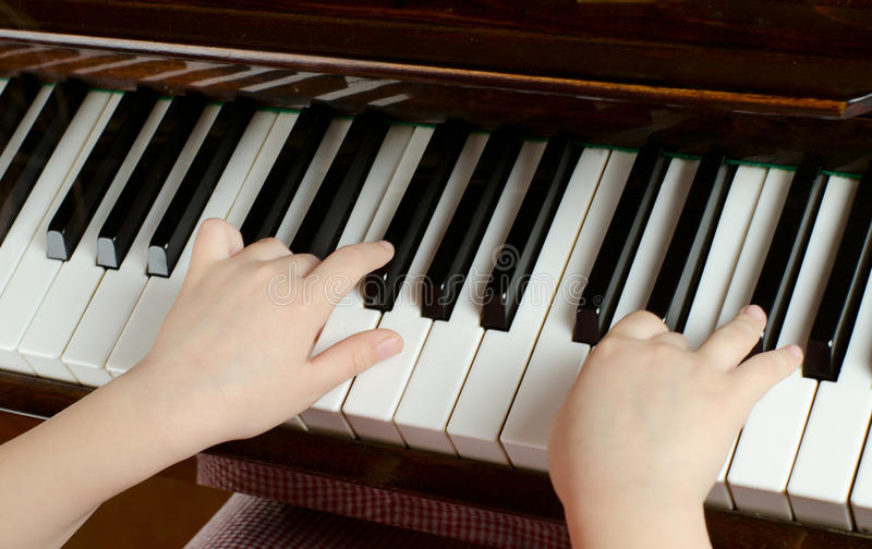 A moça aprende jogar um piano fotografia de stock royalty free