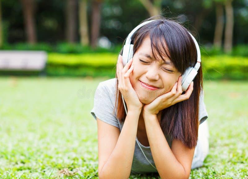 A moça asiática aprecia escuta a música foto de stock