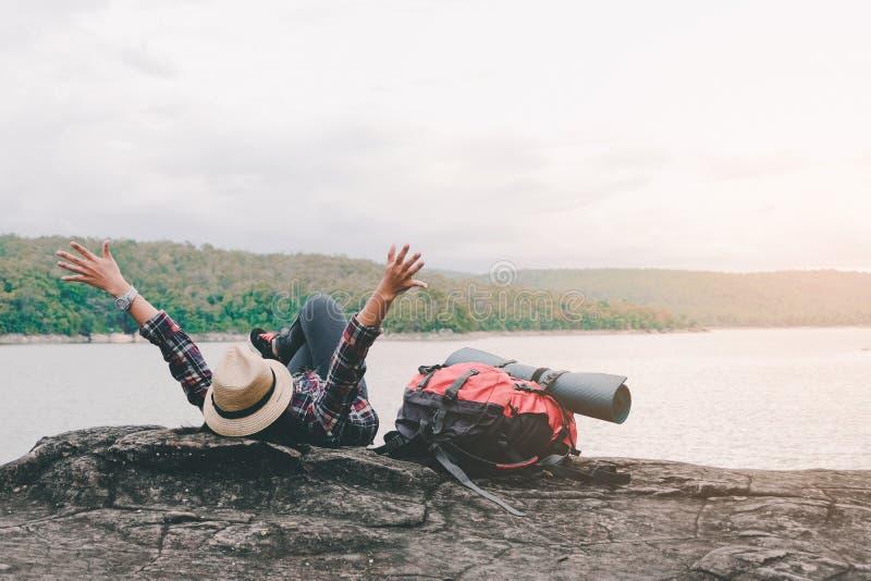 Moça asiática do moderno com trouxa que aprecia o por do sol na montanha máxima Conceito da aventura do estilo de vida do curso imagens de stock