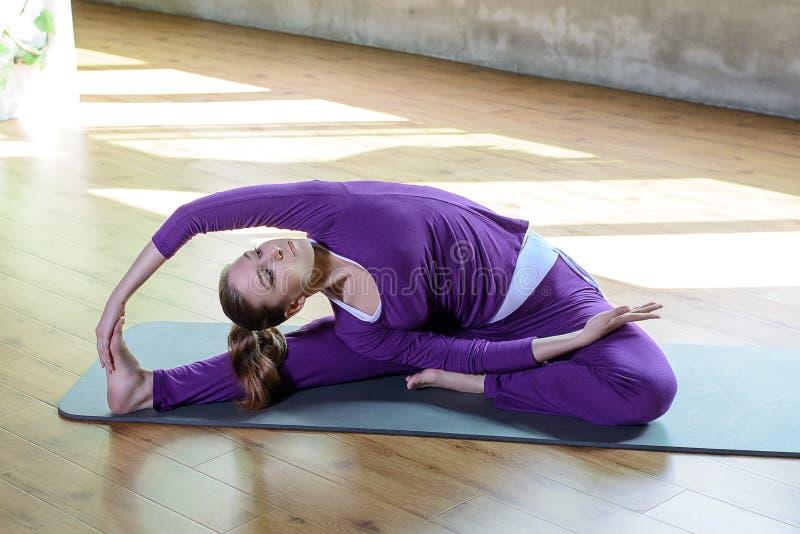 A moça atlética bonita faz a prática da ioga interna, esticando pilates relaxa o tempo fotografia de stock