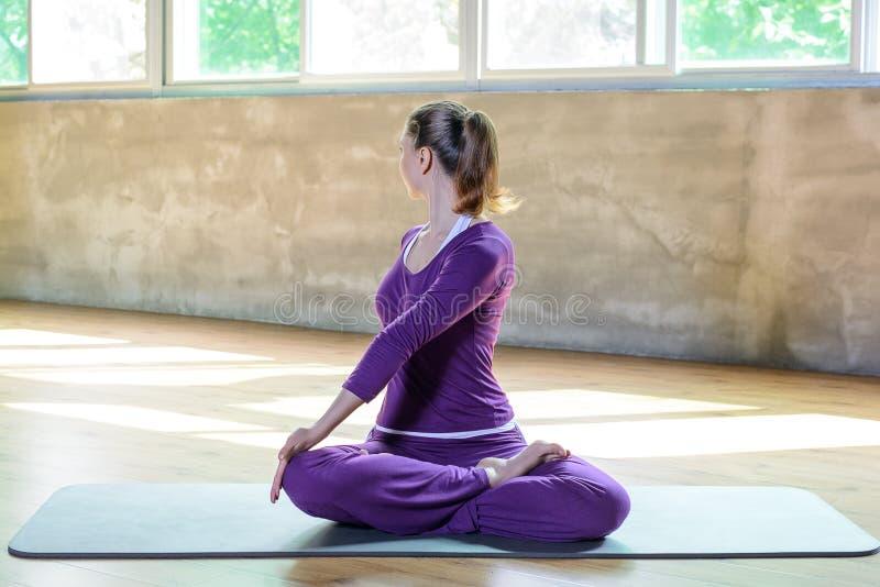 A moça atlética bonita faz a prática da ioga interna, pilates do bem-estar relaxa o tempo fotos de stock