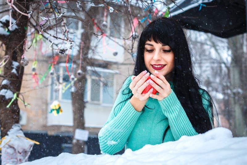 A moça atrativa bebe um coffe no café da rua em wi nevado fotos de stock