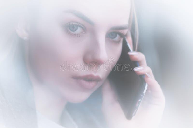 Moça atrativa do retrato do close up que fala no olhar do telefone na câmera opinião do Não-contraste com a reflexão de imagens de stock royalty free