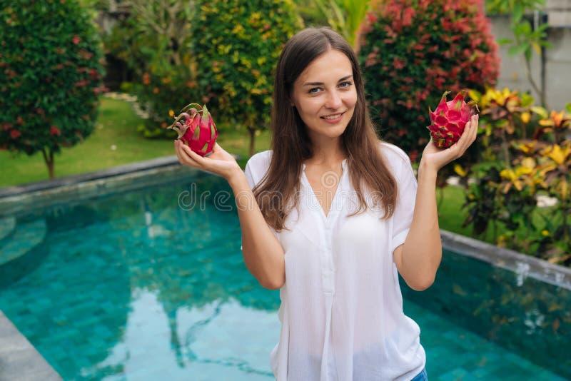 Moça atrativa do retrato que guarda dois frutos do dragão, pitaya em suas mãos perto da associação imagens de stock