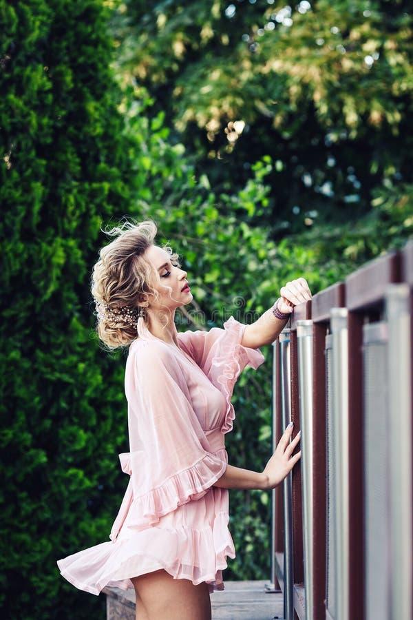 Moça atrativa em um vestido cor-de-rosa curto que levanta perto de uma cerca de aço no fundo da folha verde imagem de stock