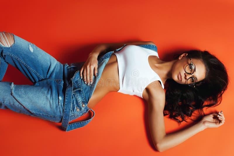 Moça atrativa no estilo do desgaste das calças de brim da sarja de Nimes fotos de stock royalty free