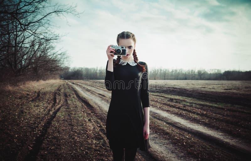 Moça atrativa no vestido preto que toma imagens pela câmera clássica do filme Retrato exterior no campo fotos de stock