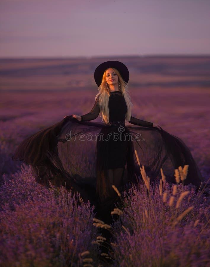 A moça bonita anda em um campo da alfazema imagens de stock