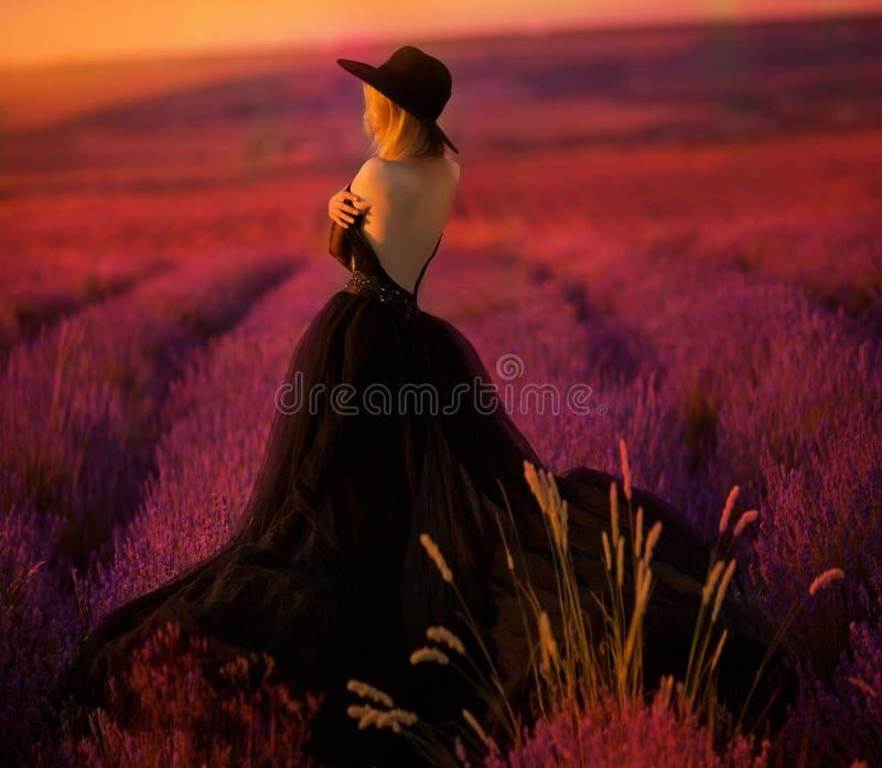 A moça bonita anda em um campo da alfazema imagem de stock