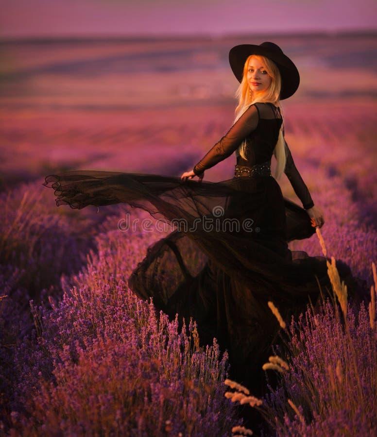 A moça bonita anda em um campo da alfazema imagens de stock royalty free