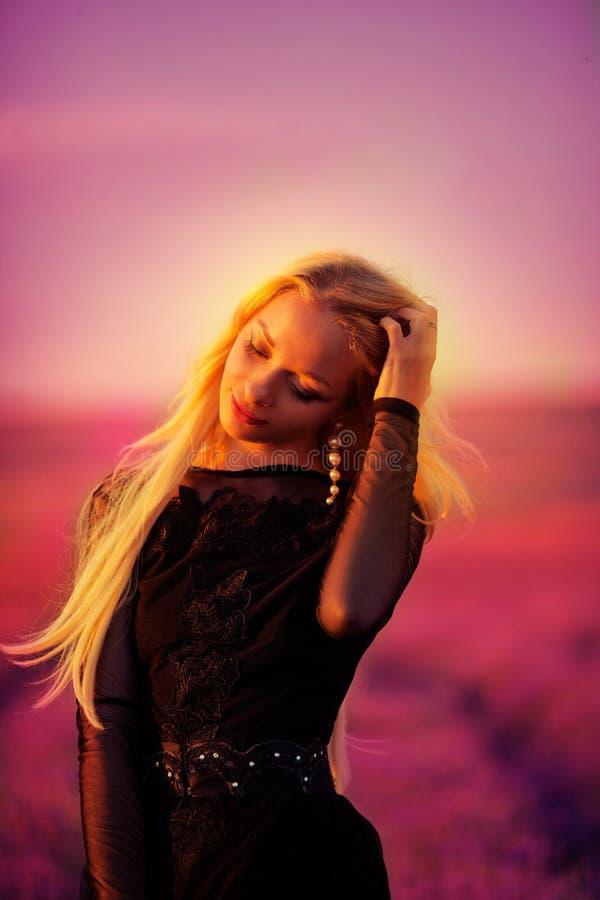 A moça bonita anda em um campo da alfazema fotografia de stock