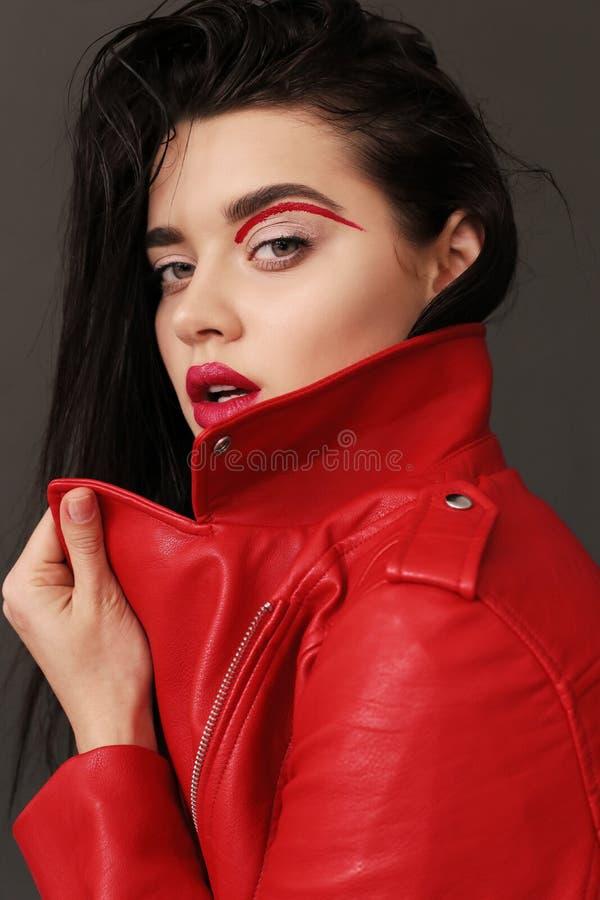 Moça bonita com cabelo escuro e pele de incandescência no leat vermelho foto de stock