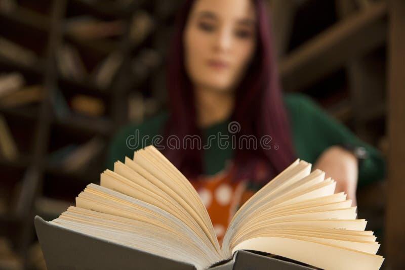 A moça bonita com cabelo longo lê um livro na biblioteca imagem de stock royalty free