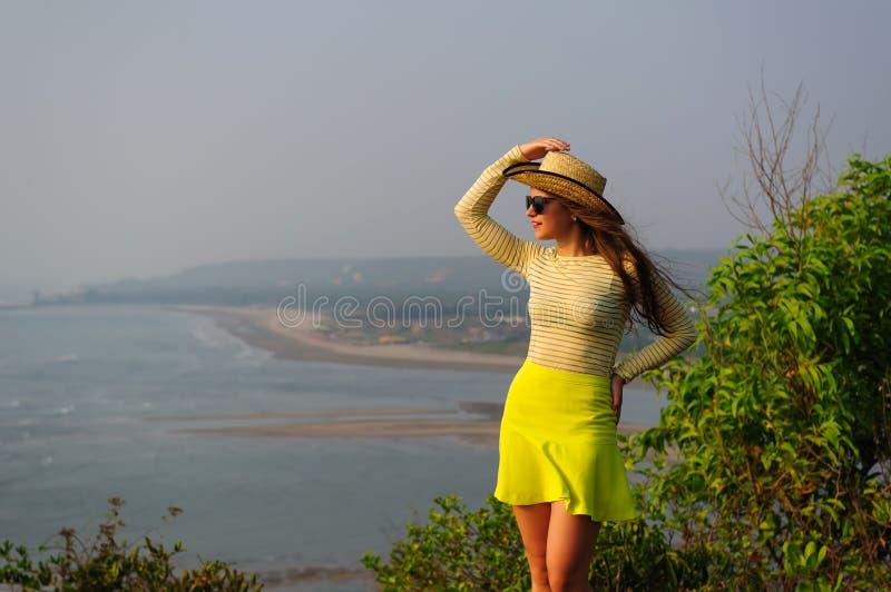 A moça bonita com cabelo longo no chapéu de palha, em vidros escuros e na saia amarela curto está na parte superior contra o lito imagem de stock royalty free