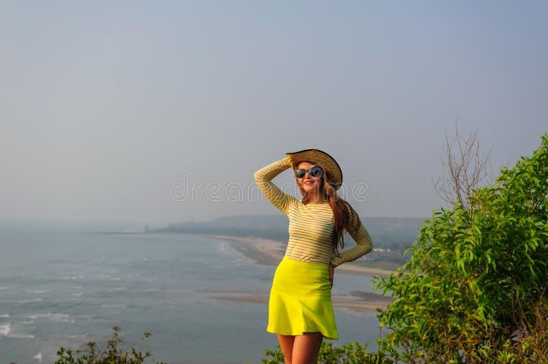 A moça bonita com cabelo longo no chapéu de palha, em vidros escuros e na saia amarela curto está na parte superior contra o lito foto de stock royalty free