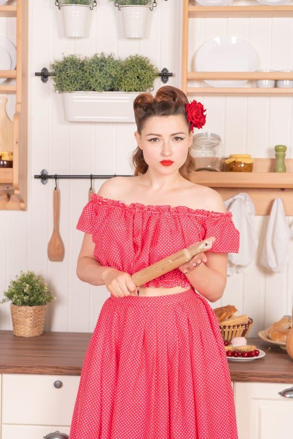 Moça bonita com a flor em seu cabelo que levanta no pino vermelho acima do vestido do às bolinhas em casa na cozinha fotografia de stock