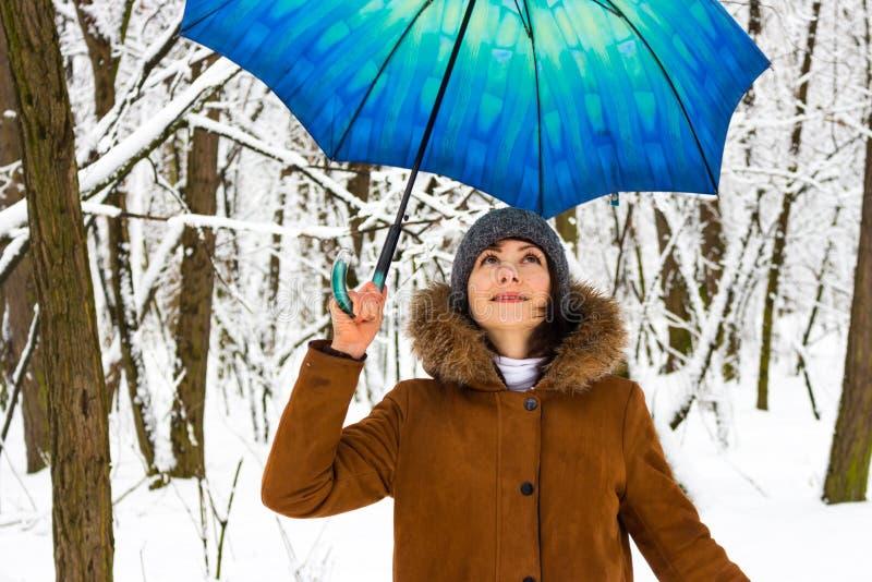 Moça bonita com o guarda-chuva azul no conceito nevado da queda de neve da floresta Mulher sob a chuva molhada da neve no parque  imagem de stock