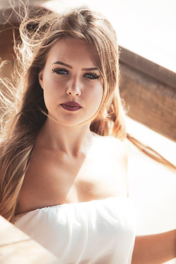 Moça bonita com olhos azuis e cabelo louro no vento imagem de stock royalty free