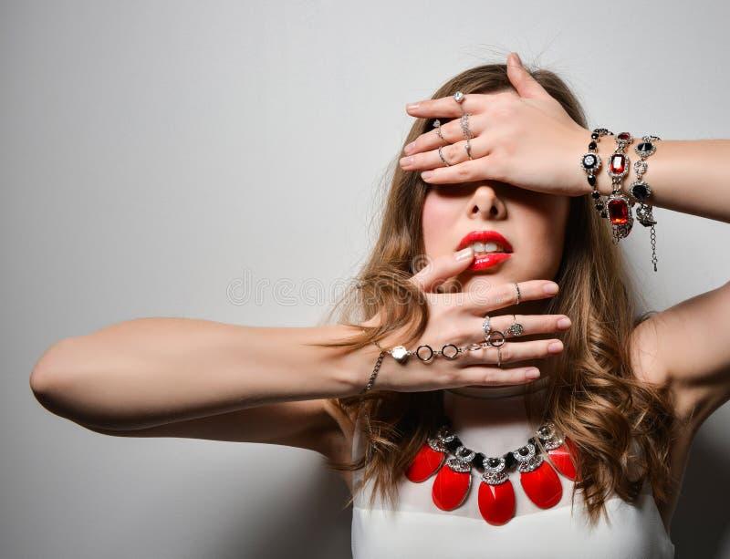 Moça bonita com os bordos brilhantes no estúdio Bijutaria da joia - brincos, bracelete, colar vermelha fotos de stock
