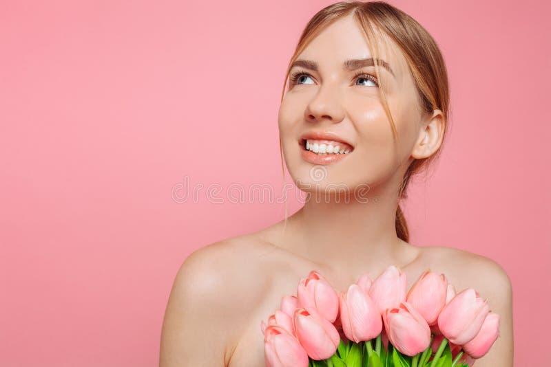 Moça bonita com a pele limpa que guarda um ramalhete de tulipas cor-de-rosa, em um fundo cor-de-rosa imagem de stock
