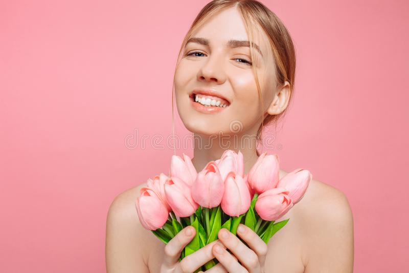 Moça bonita com a pele limpa que guarda um ramalhete de tulipas cor-de-rosa, em um fundo cor-de-rosa fotos de stock royalty free