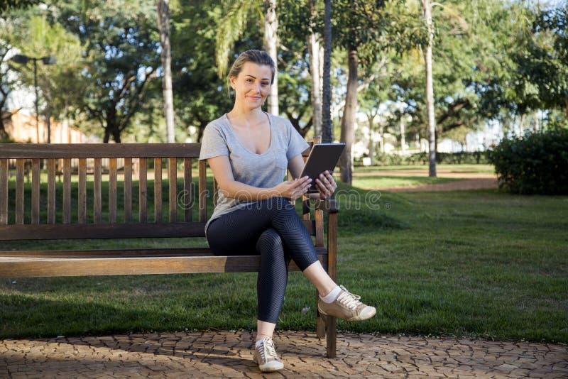 Moça bonita com portátil ou tabuleta no parque imagem de stock royalty free
