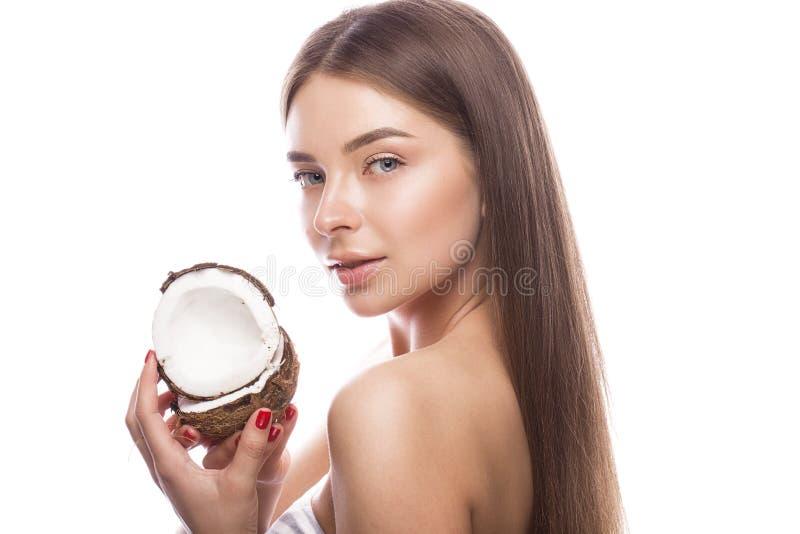 Moça bonita com uma composição natural clara e pele perfeita com o coco em sua mão Face da beleza imagem de stock