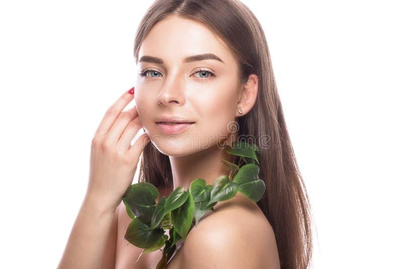 Moça bonita com uma composição natural clara e pele perfeita com ramo verde em sua mão Face da beleza fotografia de stock royalty free