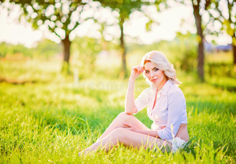 Moça bonita de sorriso que senta-se na grama no jardim fotografia de stock royalty free